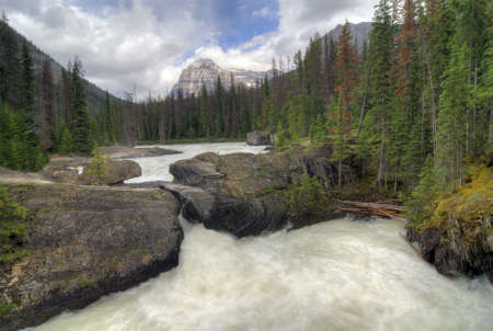 bridge in nature: The Natural Bridge in Yoho National Park in British Columbia Canada. The rugged Rocky Mountains as a backdrop.