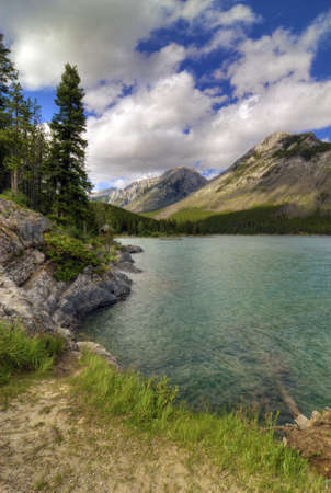canadian rockies: Lake Minnewanka in Banff Natinoal Park Canada. Surrounded by the Rocky Mountains this man made lake is a popular area for fishing and boating.  Stock Photo