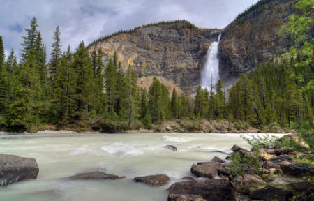 thundering: The thundering waters of Takakkaw Falls in Yoho National Park in British Columbia Canada. This popular tourist attraction features the turquoise blue waters of glacier melt. It tumbles down 830 feet into the Yoho river below. Stock Photo