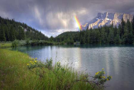 밴프 국립 공원 캐나다에서 밴프 근처 캐스케이드 연못에 마운트 런들 통해 아름 다운 무지개. 이 그림 연못은 록키 산맥에 둘러싸여있다.