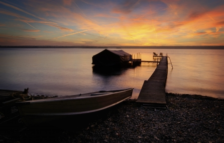 A beautiful autumn sunrise on the pebbled shores of Lake Cayuga in the Finger lakes region of New York state  A row boat with oars is docked on the side of a pier that leads out to a power boat shelter and a deck with chairs for watching the sunrise   Reklamní fotografie