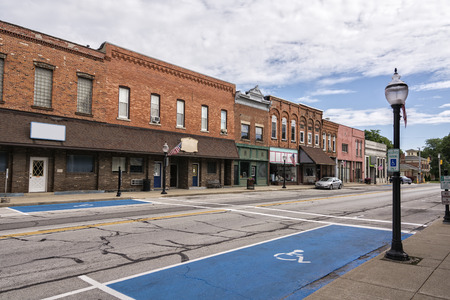 A photo of a typical small town main street in the United States of America  Features old brick buildings with specialty shops and restaurants  Decorated with spring flowers and American flags  Prominent street markings for handicap parking