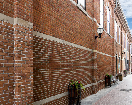 An old restored brick alley with new wrought iron flower plantsers and park benches   Stock Photo