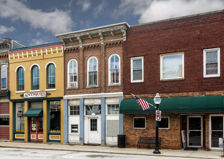 A photo of a typical small town main street in the United States of America  Features old brick buildings with specialty shops, antique stores and restaurants  Decorated with  American flags