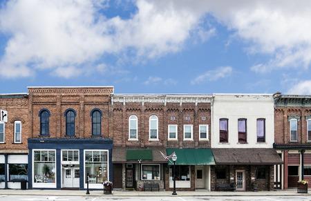 Een foto van een typisch stadje hoofdstraat in de Verenigde Staten van Amerika Eigenschappen oude bakstenen gebouwen met speciaalzaken en restaurants zijn ingericht met lentebloemen en Amerikaanse vlaggen Stockfoto