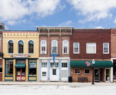 専門店やレストラン装飾アメリカの旗とのアメリカ合衆国機能の古いれんが造りの建物の典型的な小さな町のメインストリートの写真
