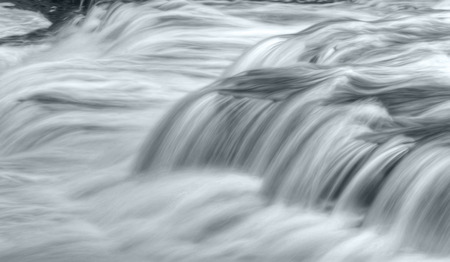 Close up of a waterfall during high water flow. Taken with a slow shutter speed to smooth out the flow of the water as is rushes by. 版權商用圖片
