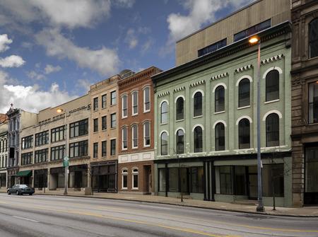 Une photo d'une rue principale d'une petite ville typique des États-Unis d'Amérique. Caractéristiques anciens bâtiments de briques avec des magasins et des restaurants spécialisés. Décoré avec des fleurs de printemps et des drapeaux américains.