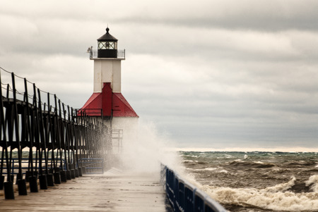 A small lighthouse out on a pier in St. Joesph Michigan during stormy weather with waves crashing into the pier.