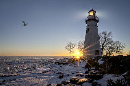 The historic Marblehead Lighthouse in Northwest Ohio sits along the rocky shores of the frozen Lake Erie. Seen here in winter with a colorful sunrise, snow on the ground and a segull flying by.