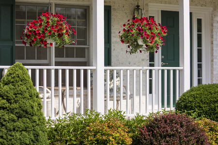 A beautiful landscaped American front porch with white railings and hanging baskets with red flowers. Stock Photo