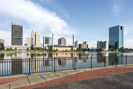 A  panoramic view of downtown Toledo Ohios skyline from across the Maumee river at a popular restaurant area with a paver brick boardwalk and a decorative iron railing..  A beautiful  blue sky with white clouds for a backdrop. Фото со стока