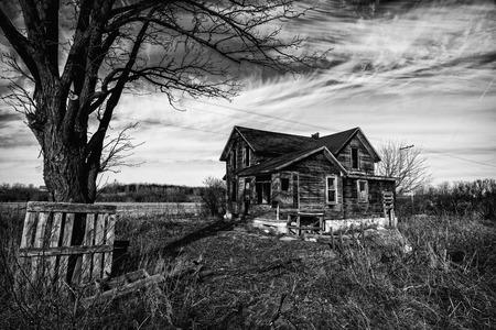 Zwart-wit foto van een oude eng verlaten boerderij die verslechtert met de tijd en verwaarlozing.