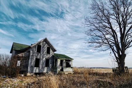 Foto van een oude eng verlaten boerderij die is deterating met de tijd en verwaarlozing. Uitgebreid met een oude boom en de lus van een beul toped met een dramatische hemel. Stockfoto