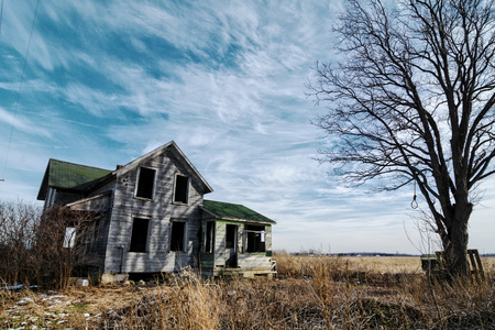 Photo of an old scary abandoned farm house that is deteriorating with time and neglect.  Enhanced with an old tree and a hangmans noose toped off with a dramatic  sky. Stock Photo