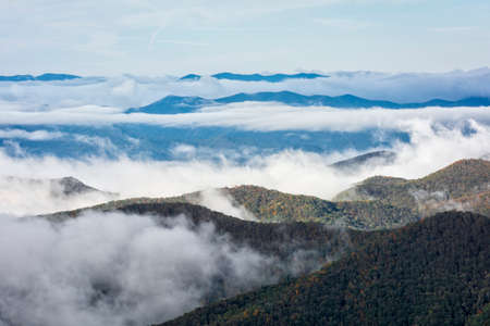 Early morning fog settles into the valleys of the mountains along the Blue Ridge Parkway in Western North Carolina on a crisp autumn October day. Stock Photo