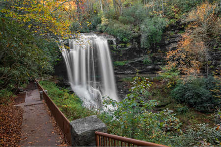 Dry Falls is a scenic 65 foot waterfall close to Highlands North Carolina. As you can see from the photo you can walk behind the waterfall. Seen here in autumn.