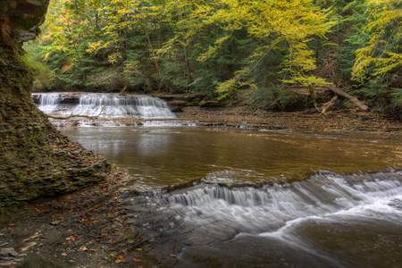 Beautiful autumn colors on the trees frame this broad waterfall.  The waterfall is called Quarry Rock Falls and is found in the South Chagrin Reservation of the Cleveland Ohio Metroparks.