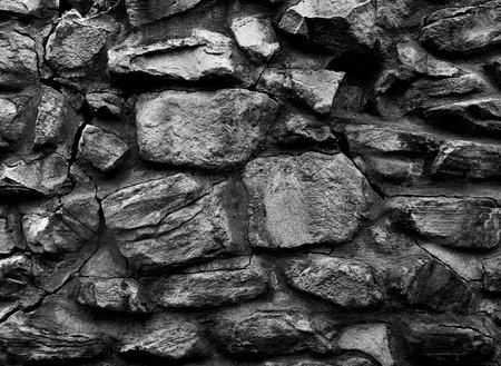 黒と白の3Dテクスチャ、背景の大きな岩で作られた古い修道院の壁