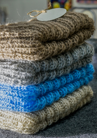Pile of four warm handmade winter hats for women blue, brown, beige and grey