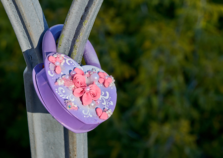 Purple wedding lock shape of a heart with a pink flowers and white pearls on the metall bridge