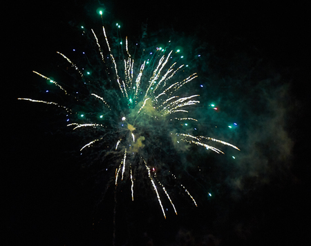 Colorful bright green fireworks and smoke in the night sky close-up background Stock Photo