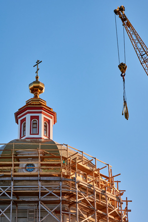 Reconstruction process of the orthodox cathedral using a crane and red bricks at golden hour under the sunlight, vertical image Stock Photo