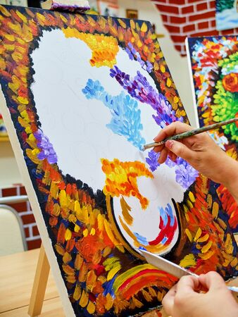 KIROV, RUSSIA - AUGUST 6, 2017: Adult woman drawing colorful bouquet on the canvas in the local art studio