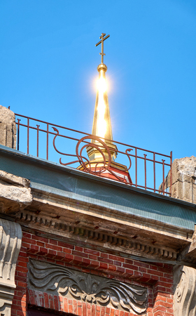 Golden dome with a cross on top shining brightly under the sunlight
