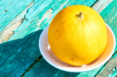 Fresh yellow melon isolated on theblue wooden table abstract summer background