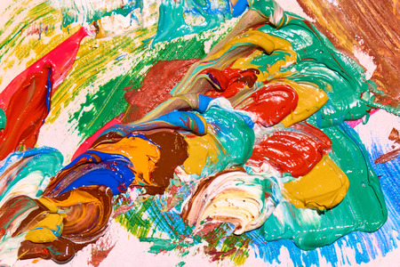 Palette covered by colorful layers of paint close-up abstract texture, backgrond