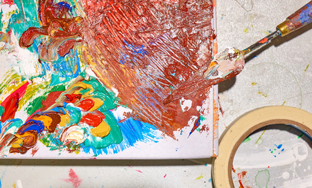 Palette and palette knife covered by colorful paint on the white table Standard-Bild
