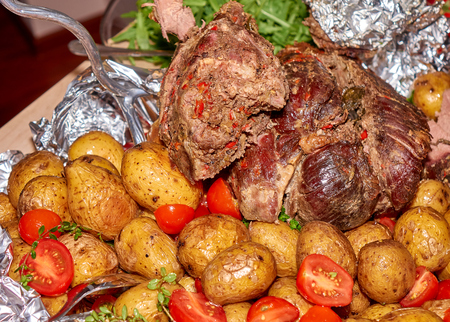 Big peace of the roasted medium well mutton meat with baked potatoes and fresh tomatoes