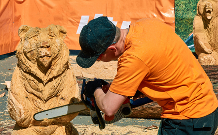 Experienced carpenter making a big wooden bear sculpture with a chainsaw during a local competition, almost finished Banco de Imagens