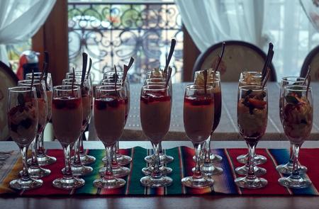 Beautiful layered desserts made of cream, berries and physalis in the tall wineglasses with a spoons standing in a row in front of a window, vintage look Stock fotó