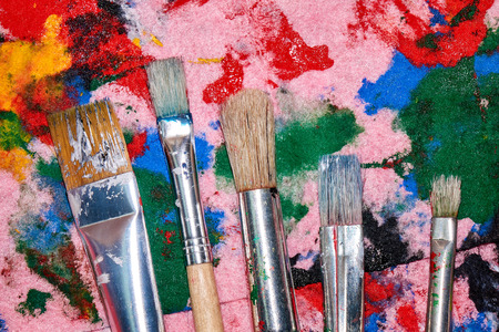 Five worn out brushes of different sizes on the messy colorful pink palette artistic background Standard-Bild