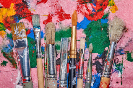 Nine worn out brushes of different sizes on the messy colorful pink palette artistic background Standard-Bild