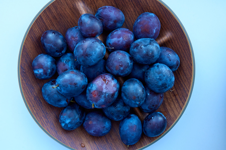 A lot of the fresh ripe plums on the wooden bowl Standard-Bild