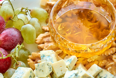 Different kinds of cheese, grapes, walnuts and honey gourment assorted close-up