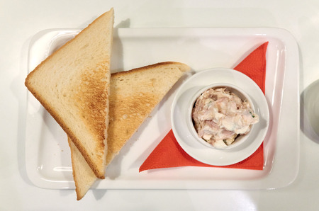 Healthy breakfast in the restaurant, tuna with a two toasts on the white background