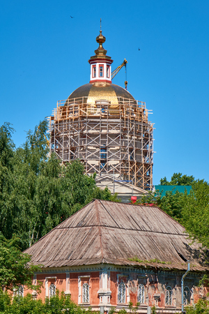 Reconstruction process of the orthodox cathedral in the russian local village using scaffolding and crane