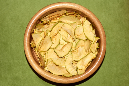 Homemade apple chips in the ceramic bowl natural healthy snack top angle view on the green background