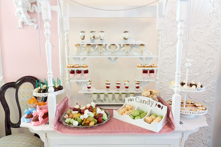 Candy bar beautifully served on the white table with a sweets, fruits, macaroons and other desserts, luxury wedding assortment