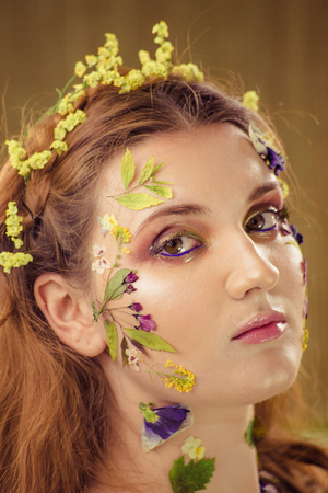 Woman with art fashion make up on face. Brown background. Stock Photo