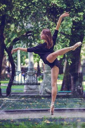 Beautiful ballerina girl in casual clothes posing on a blurred background of the park trees on background Stok Fotoğraf