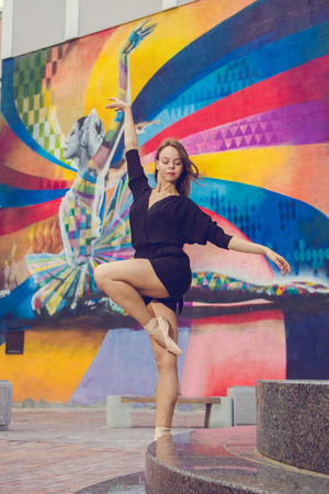 Beautiful ballerina girl in casual clothes posing on a blurred background of the city surrounded by houses, in the afternoon, dancer