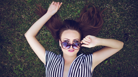 Beautiful girl resting in the park in the afternoon, lying on the grass Stock Photo