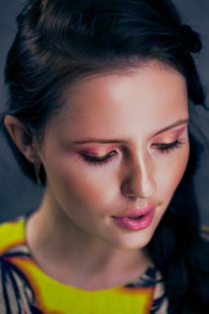 Beautiful brunette in yellow dress pink lipa pretty makeup gray background girl smiling