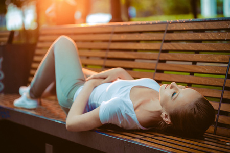 Beautiful blonde girl resting on a bench in the city Stok Fotoğraf