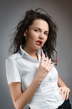 dictatorial: Sexy businesswoman with glasses in white blouse Stock Photo